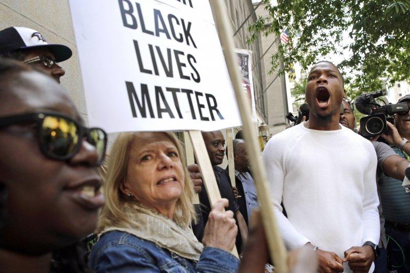 民眾23日在審理白人警官尼洛(Edward Nero)的法院外舉牌示威,牌子上寫著「黑人的生命一樣重要」。(美聯社)