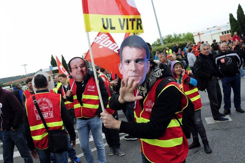 戴著法國總理瓦爾及總統奧朗德面具的抗議人士(美聯社)