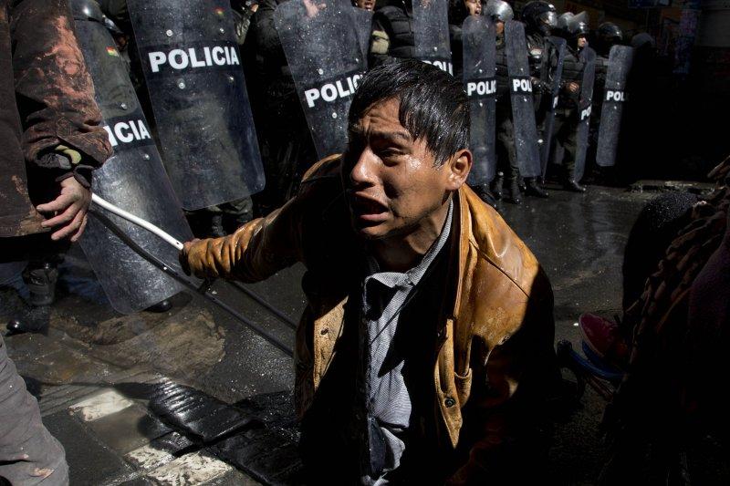 玻利維亞身障者到總統府前抗議遭水柱攻擊。(美聯社)