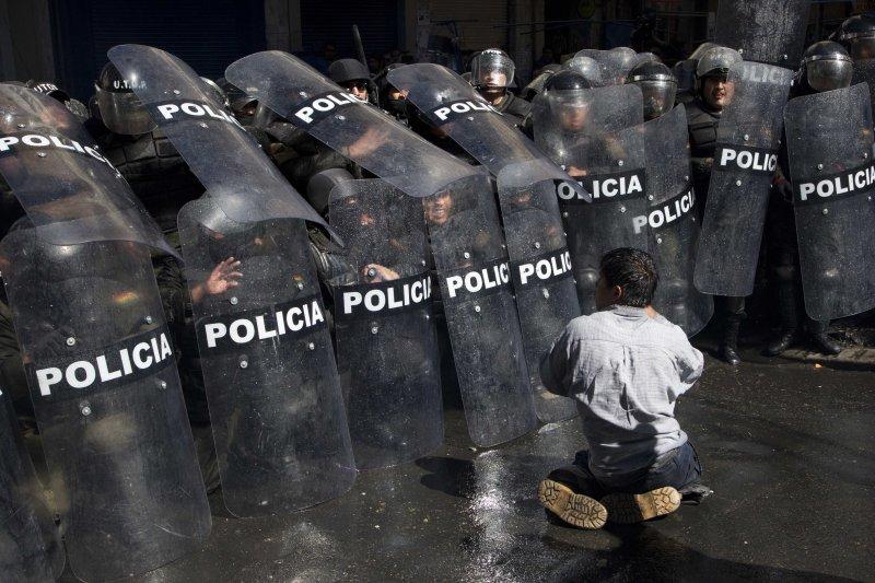 玻利維亞身障者到總統府前抗議,遭到警方以水柱攻擊。(美聯社)