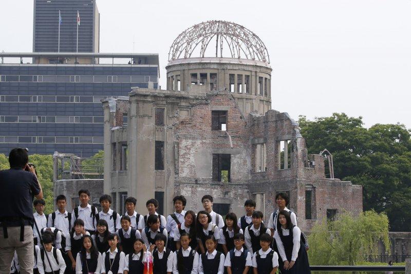 日本學童在廣島原爆留下的的建築物「原子彈爆炸圓頂屋」(Genbaku Dome)前留影。(美聯社)