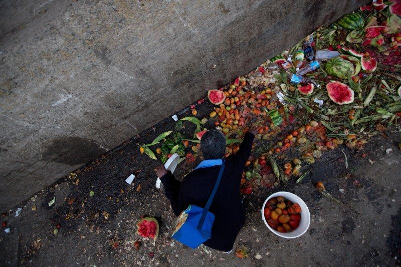 委內瑞拉民眾有錢也買不到食物,只好在菜市場的垃圾堆裡撿拾水果。(美聯社)