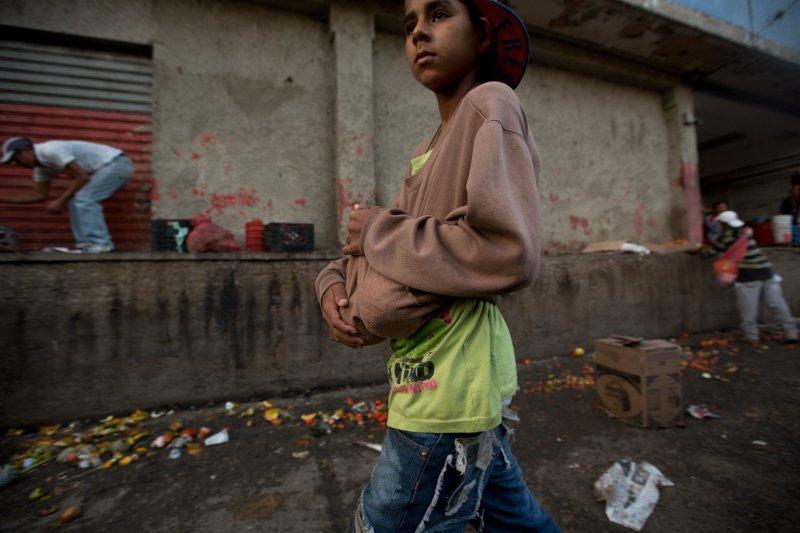 委內瑞拉民眾有錢也買不到食物,只好在菜市場的垃圾堆裡撿拾水果蔬菜。(美聯社)