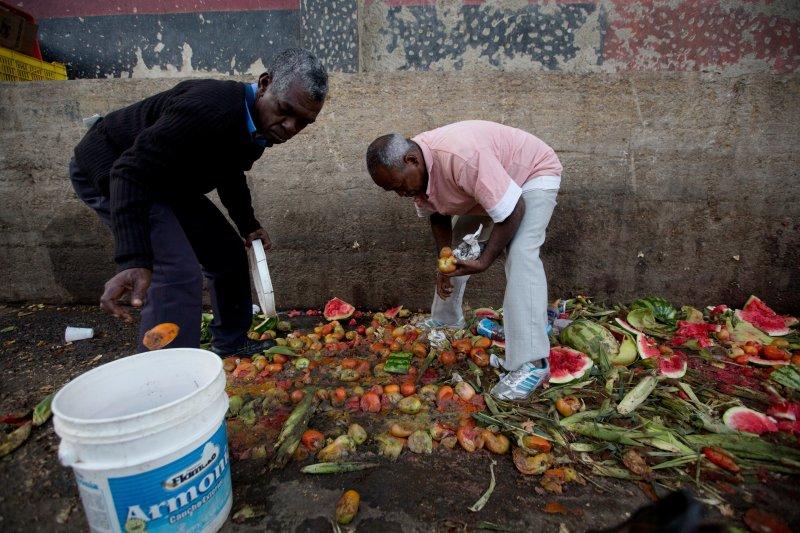委內瑞拉民眾有錢也買不到食物,只好在菜市場的垃圾堆翻找還能吃的東西。(美聯社)