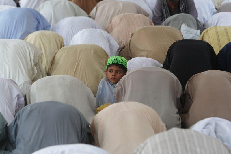 巴基斯坦的穆斯林們在齋戒月期間誠心禱告,一位並未隨同眾人跪拜的小男孩特別顯眼。(美聯社)