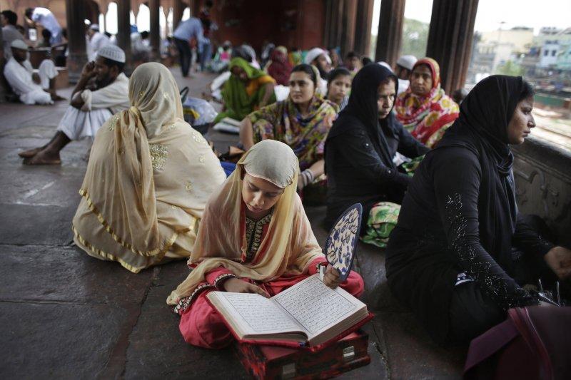 印度新德里,一位年輕的穆斯林女孩在齋戒月期間閱讀古蘭經。(美聯社)