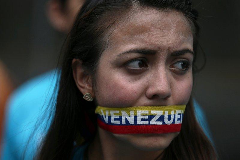 一位女性用委內瑞拉國旗顏色製成的布條封口,對政府表達無言的抗議。(美聯社)