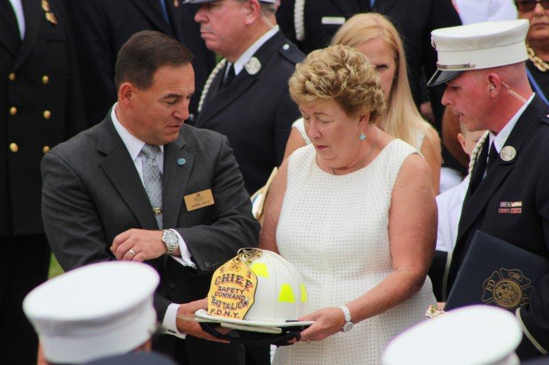 紐約消防局17日為九一一事件罹難消防員史塔克(Lawrence Stack)舉行葬禮,遺孀泰瑞莎在典禮上接過先生的頭盔。(美聯社)