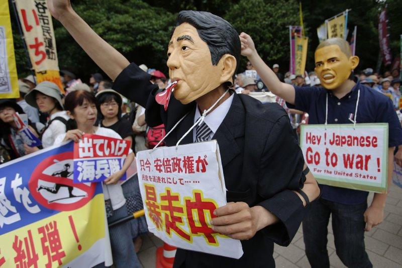 抗議駐日美軍的日本民眾19日戴上安倍與歐巴馬的頭像,諷刺他們的暴走行徑將讓日本捲入戰爭。(美聯社)