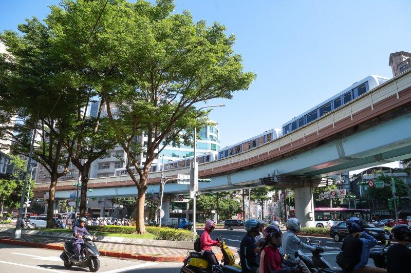 正準備行駛入台北捷運文湖線六張犁捷運站的捷運列車及一早上班的機車族。(顏麟宇攝)