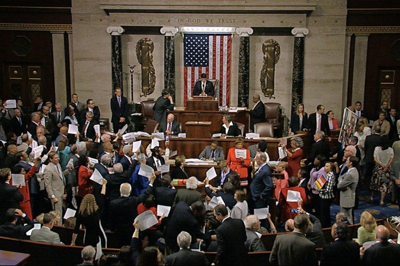 眾議院議員高舉「沒有槍管法案、沒有休息,抗議共和黨迴避表決槍枝管制法案,逕行宣布休會。(美聯社)