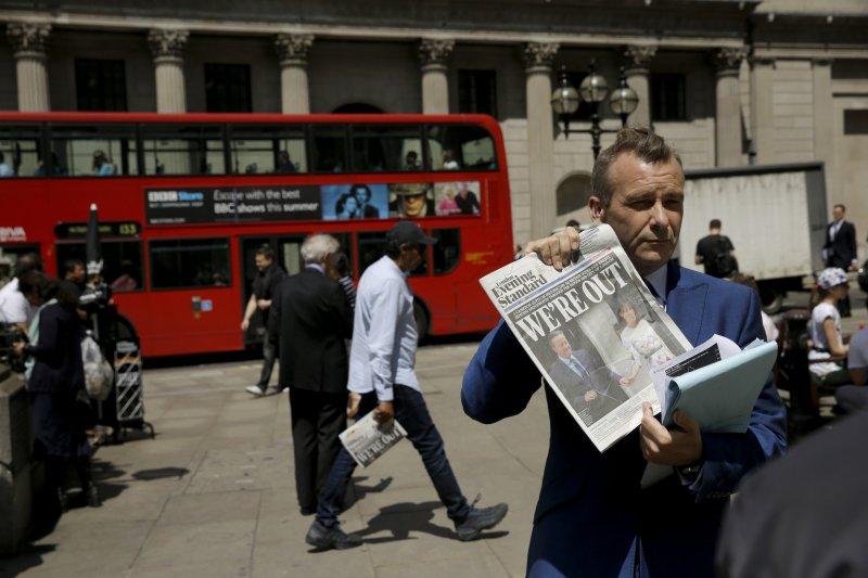 英國脫歐派勝出,一名男子展示頭版寫著「我們脫歐了」的報紙。(美聯社)