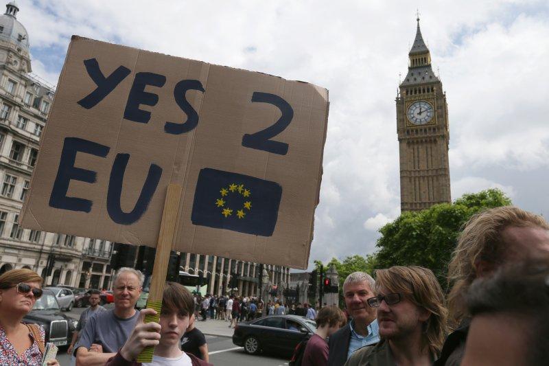 在英國脫歐公投過關後,一位支持留歐的年輕人在倫敦高舉留歐標語。(美聯社)