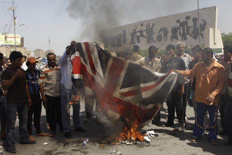 不滿英國出兵伊拉克,憤怒的伊拉克民眾焚燒英國國旗。(美聯社)