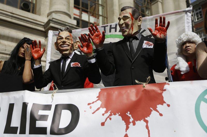 反對出兵伊拉克的民眾戴上布萊爾的面具,在布萊爾的家門前抗議。(美聯社)