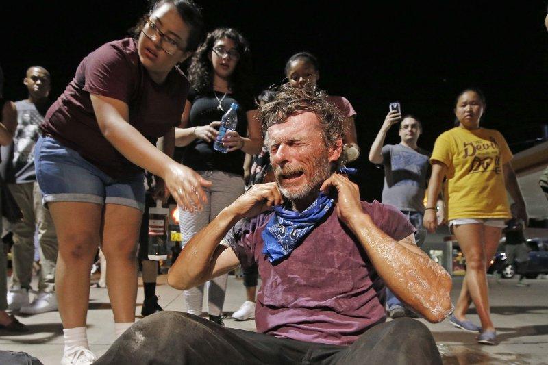 美國種族歧視抗議衝突升高,示威民眾遭警方丟擲催淚彈坐倒在地。(美聯社)