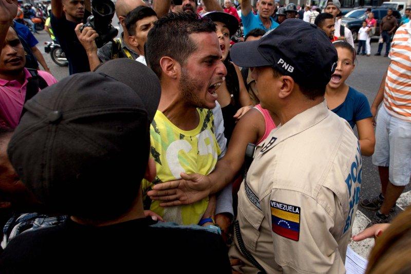 排隊苦等購買日用品不可得的委內瑞拉民眾,怒罵在現場維持秩序的警察。(美聯社)