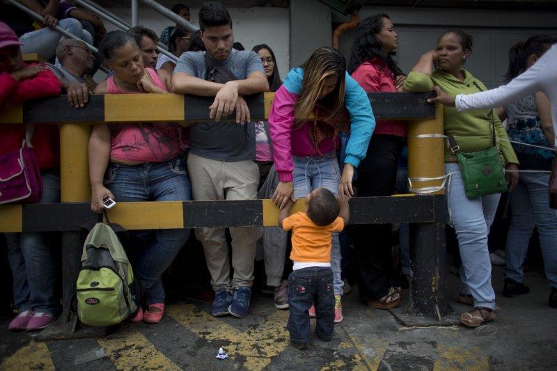 委內瑞拉首都的一間超市外,許多民眾正在排隊等候購買日用品。一位16歲的小媽媽正在安撫她年僅一歲的孩子。(美聯社)