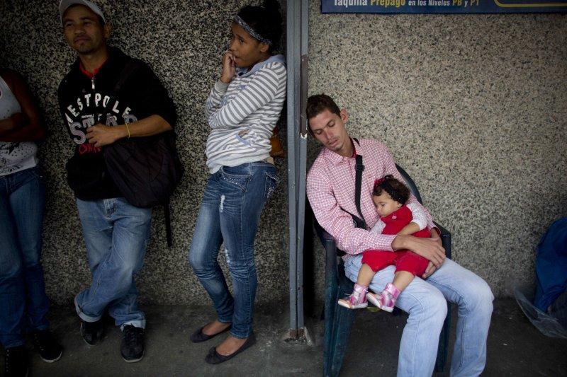 委內瑞拉首都的一間超市外,許多民眾正在排隊等候購買日用品。一位爸爸抱著自己的女兒不耐久候,雙雙入睡。(美聯社)