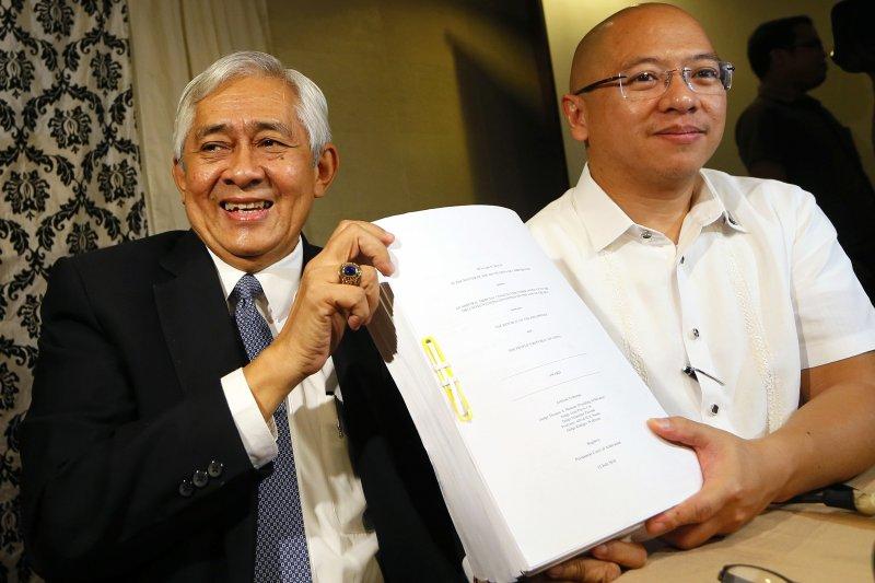 菲律賓最高法院大法官哈爾德勒薩(Francis Jardeleza,左)與總檢察長希爾拜(Florin Hilbay)一起展示剛出爐的南海仲裁判斷。(美聯社)