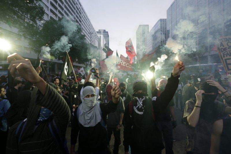 里約熱內盧的學生6日走上街頭高舉抗議火把,表達對政府花費鉅資舉辦奧運、忽視教育議題的不滿。(美聯社)