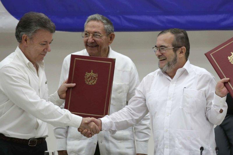 哥倫比亞總統桑托斯(左)和FARC領袖西梅內斯(右)在哈瓦那簽署停火協議,古巴總統勞爾・卡斯楚居間作證。(美聯社)
