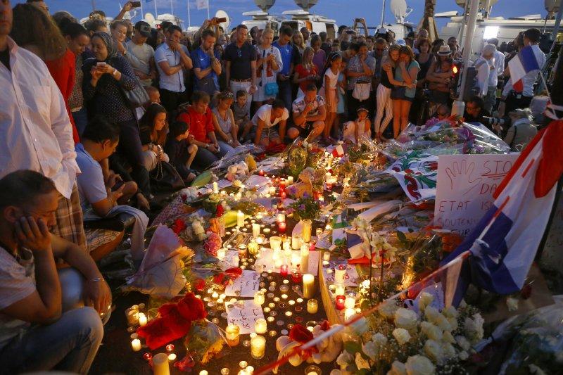 尼斯恐攻的事發地點15日堆滿蠟燭、鮮花、玩具,民眾也聚集在一起悼念遇害者。(美聯社)法國國慶日恐攻