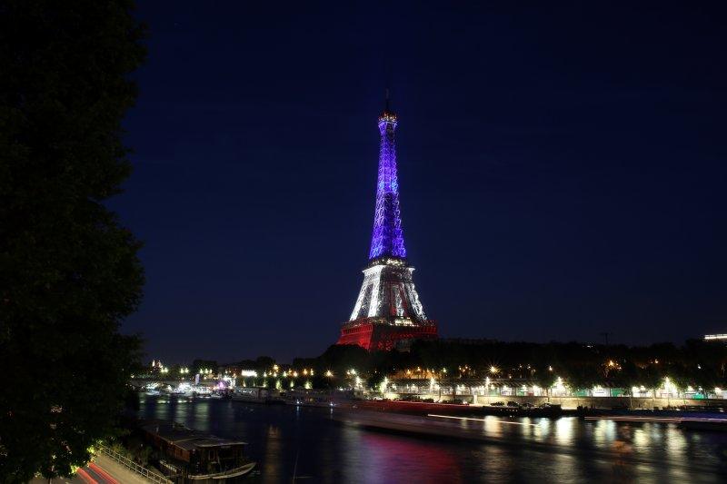 巴黎艾菲爾鐵塔15日投上藍白紅三色,哀悼尼斯的恐攻受害者。(美聯社)法國國慶日恐攻