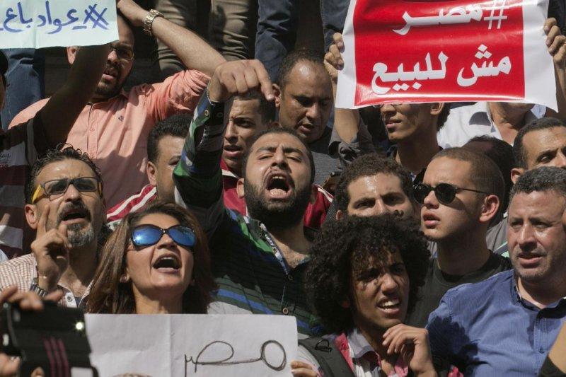 埃及抗議者在今年4月15日一場街頭抗爭中叫喊著反對總統塞西的標語,埃及國家安全局則施放催淚瓦斯驅離逮捕抗議人群。(美聯社)