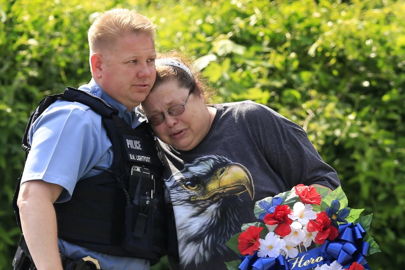 堪薩斯市警官梅爾頓19日殉職,友人前往案發地點哀悼致意。(美聯社)