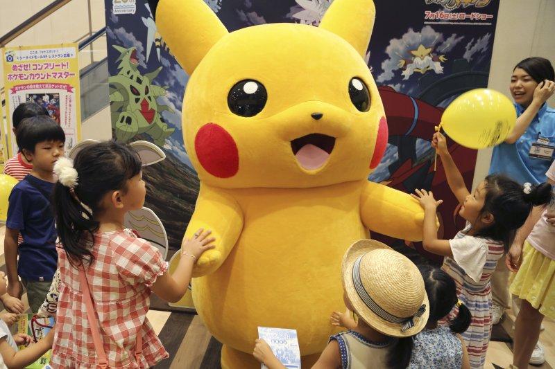 東京的小朋友正在跟皮卡丘大型人偶玩樂。(美聯社)