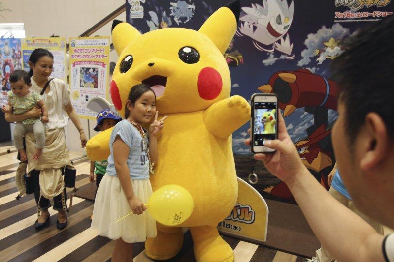 日本的小朋友在百貨公司跟皮卡丘合照。(美聯社)