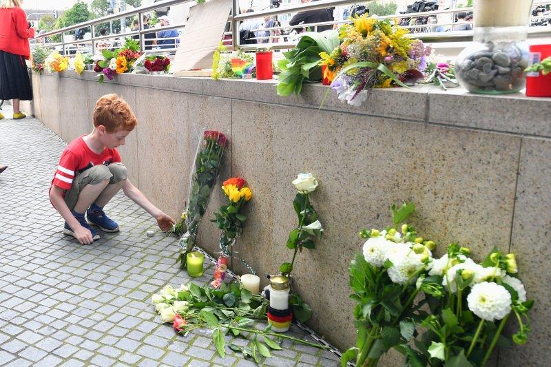 一名孩童在案發現場向慕尼黑槍擊案受害者獻花致哀。(美聯社)