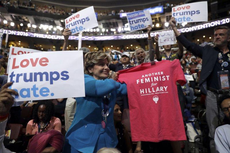 美國民主黨全國大會(DNC)25日在賓州第一大城費城(Philadelphia)登場,支持者手持「愛川普們所恨」(Love Trumps Hate)的標語(美聯社)