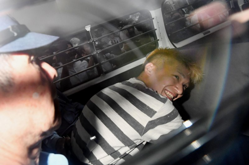 「津久井山百合園」屠殺案的兇嫌植松聖在離開警局時,臉上明顯帶著笑容。(美聯社)