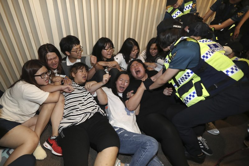 南韓大學生28日闖入慰安婦支援財團「和解.平癒財團」的成立會場抗議。(美聯社)