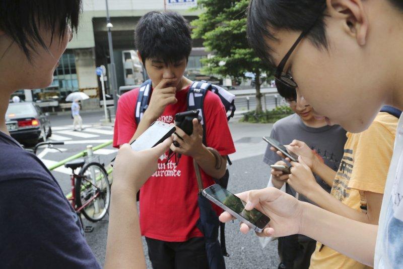 年輕人在街頭玩Pokémon GO造成部份交通問題,引發批評,但呂秋遠的看法是...(美聯社)