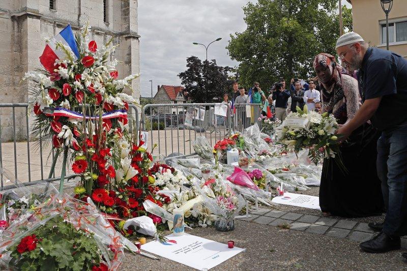 法國穆斯林聚集在遭到攻擊的教堂外,悼念遭恐怖分子殺害的天主教神父與教徒(美聯社)