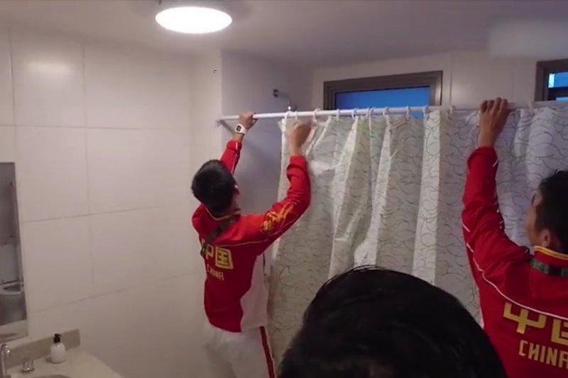 里約奧運開幕在即,選手村設施還七零八落,圖為中國桌球選手自行安裝浴簾。(圖/新華社)