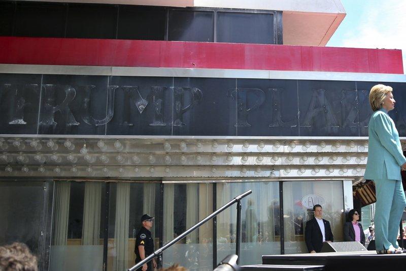 希拉蕊在歇業的亞特蘭大川普賭場舉行活動,後方牆上隱約可見川普名字。(美聯社)