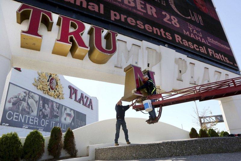工人拆除川普賭場的招牌。(美聯社)