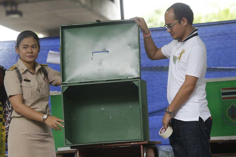 泰國7日舉行新憲草案公投,選務人員在投票開始前讓民眾檢視票匣。(美聯社)