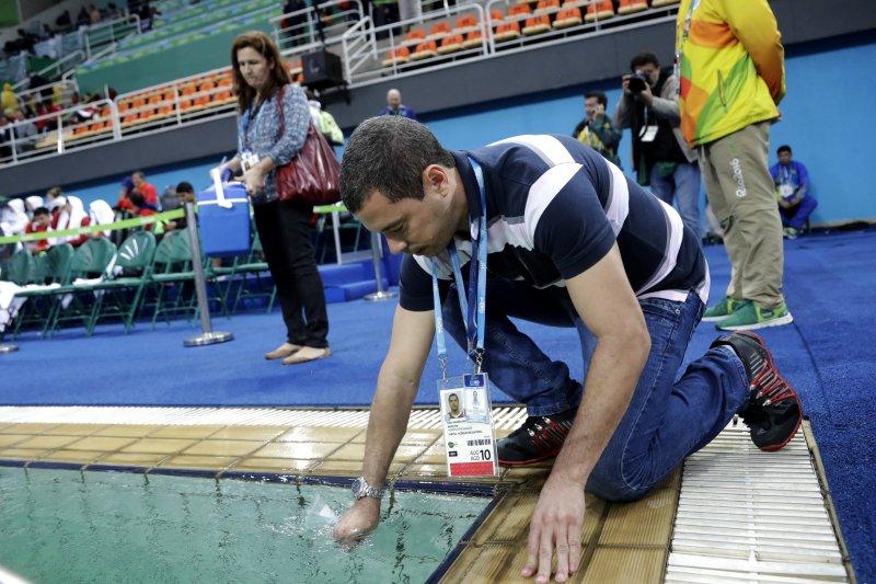 奧運工作人員正在取樣檢驗水質。(美聯社)