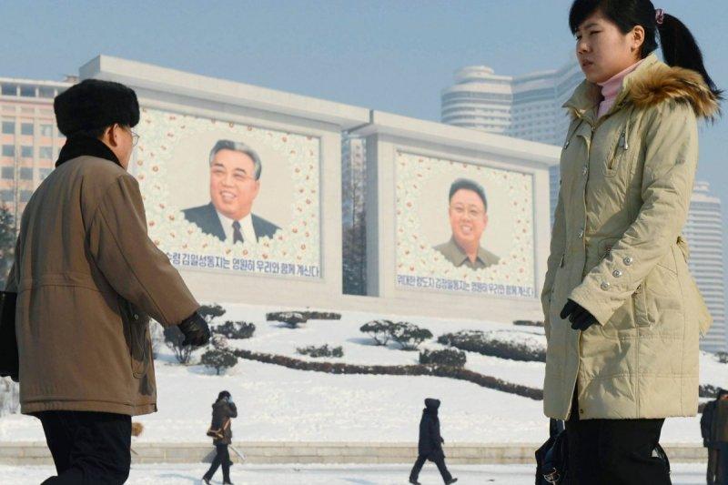 北韓開國領袖金日成(左)和其子二代領導人金正日(右)的肖像高掛在北韓街頭。(美聯社)