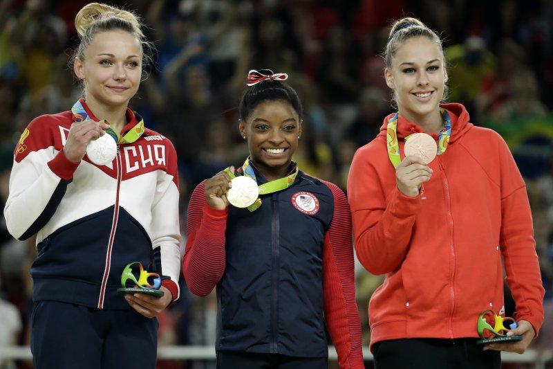 美國體操名將拜爾斯在里約奧運的女子跳馬項目摘金,左右是比她高出一個頭的銀牌帕塞卡、銅牌斯泰因博格。(美聯社)