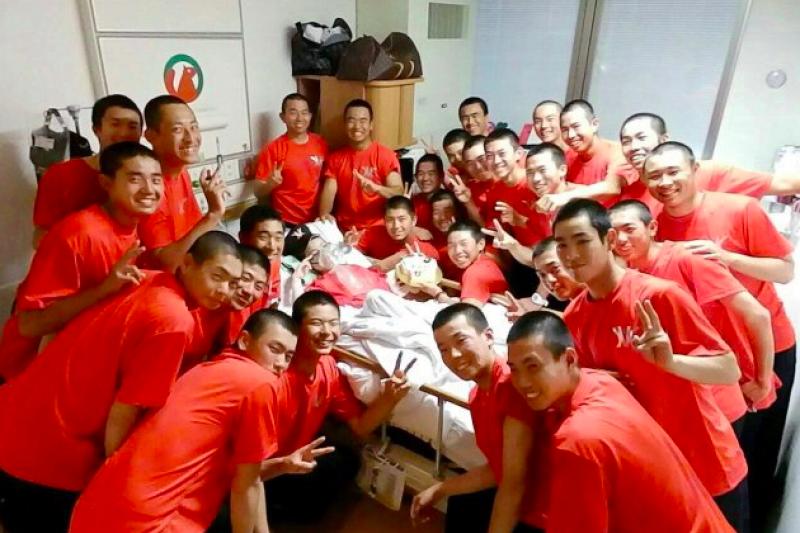 臥病在床的亞美在球隊隊友包圍下露出開心的笑容。(圖/twitter)