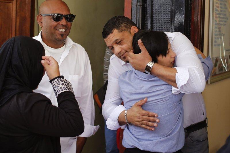 南非法庭判決偷走女嬰的女子坐牢10年後,失蹤女嬰薩芬妮(Zephany Nurse)的原生父母互相擁抱。(美聯社)