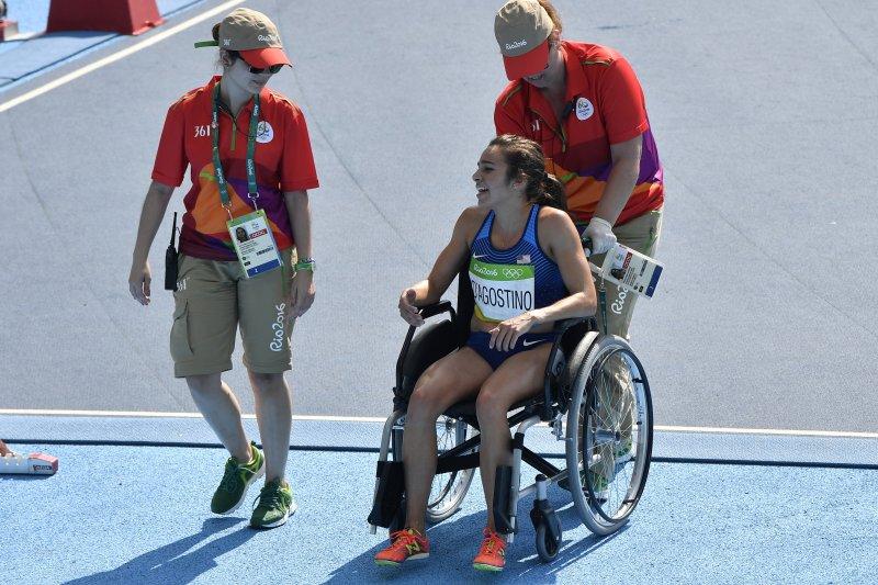 美國田徑選手迪阿寇斯蒂諾完成賽事後,由工作人員推著輪椅下場。(美聯社)