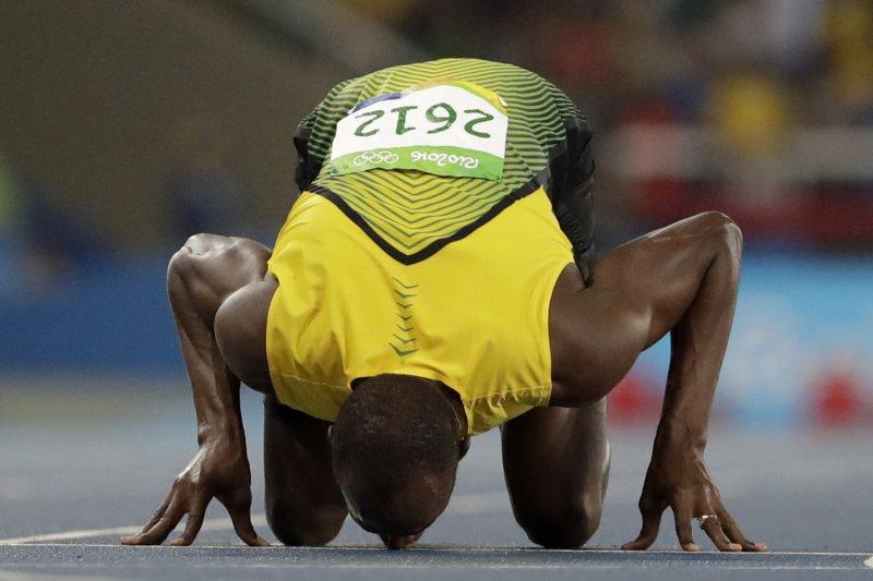 短跑名將「牙買加閃電」博爾特(Usain Bolt)摘金後,親吻地板(美聯社)