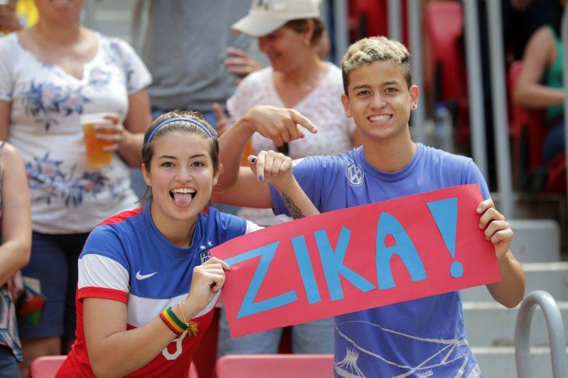 美國球迷在里約奧運女子足球賽的場邊,對媒體鏡頭舉起茲卡病毒的標語。(美聯社)